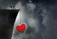 Couple rescuing relationship by pulling heart on rope over edge of cliff