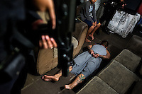 An alleged gang member lies on the floor, handcuffed by the special anti-gang unit (Unidad Antipandillas) during a night raid in Soyapango, a gang neighborhood in San Salvador, El Salvador, 13 December 2013. Although the murder rate in the country has dropped significantly, after a truce between two major street gangs (Mara Salvatrucha and Barrio 18) was agreed in 2012, the lack of security and violence are still the main issues in people's daily life. Due to the fact the gangs have never stopped their criminal activities (extortions, distribution of drugs and kidnappings), the Police anti-gang forces keep running their operations and chasing the 'homeboys' (how the gang's foot soldiers usually call themselves) in the poor, socially deprived suburbs of Salvadoran cities.