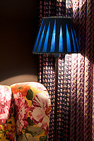 An armchair covered in a contemporary floral chintz next to a standard lamp with a royal blue shade in the living room
