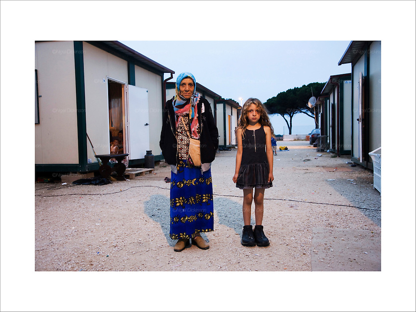 A woman and her grand-daughter living in a 'container camp'. This concentraion camp type environment, is close to a motorway,  but far away from public amenities, schools and shops. Before they lived happily in Vicolo Savini inside Rome itself. Castel Romano, Italy 2008..Roma Gypsies left Rajasthan in India a thousand years ago, in the ninth and tenth centuries. They were pushed west by the Ottoman Muslim Empire as it moved through Persia towards the frontiers of Europe. They entered Europe in the foutrteenth century and were slaves in Romania and Moldavia until the mid 1850s. There are about 15 million Roma gypries in the world, about 12 million who live in Europe. they are Europe's largest ethnic minority. They have rich traditions and culture, their own language. They are renowned for their prowess in music and dance; they are also skilled craftsman, metal roofmakers, silver and goldsmiths. Their traveling and nomadic lifestyle which grew from a necessity to find work, and because they were often moved on from one place to the next, has given them both a liberty but also marks them as different and they are often feared by sedentary peoples, who label and scapegoat them. They are hardy survivors and live in the brunt of racism and prejudice, often marginalised, living in poverty, without proper human rights afforded to them..