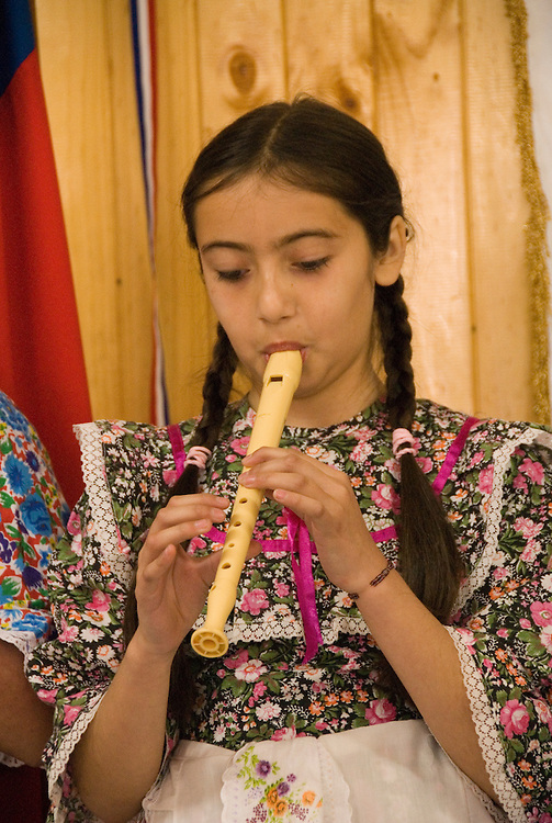 Chile, Lake Country: Children at one room rural schoolhouse in Peulla.  Girl playing flute..Photo #: ch671-33930.Photo copyright Lee Foster www.fostertravel.com, lee@fostertravel.com, 510-549-2202.