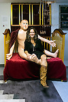 Massapequa, New York, USA. September 18, 2014. LORI HOROWITZ, artist and gallery owner, is sitting on her sculpture, Truths Without Consequences, a gigantic naked baby on an open crib, during the Studio 5404 Art Space opening reception for the art show Taking it to the Street. The installation she is interacting with is sculpted epoxy, wood, fabric and copper, and the exhibit features new works by emerging and up-and-coming local and New York artists. Studio 5404 is on the South Shore of Long Island.
