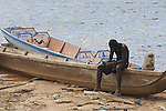 Maroon man resting on a dugout canoe in the port town of Affobaka on the Brokopondo reservoir, Suriname.