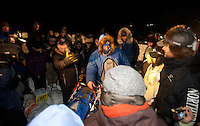 A crowd surrounds 2011 Iditarod leader John Baker as his arrives in the Unalakleet checkpoint on Sunday.