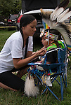 Native American , Chaske Hill Sicangu Lakota and Seneca , mother dressing and preparing of her 3 year old son for pow wow dance contest at the Thunderbird powwow in Queens, NY .