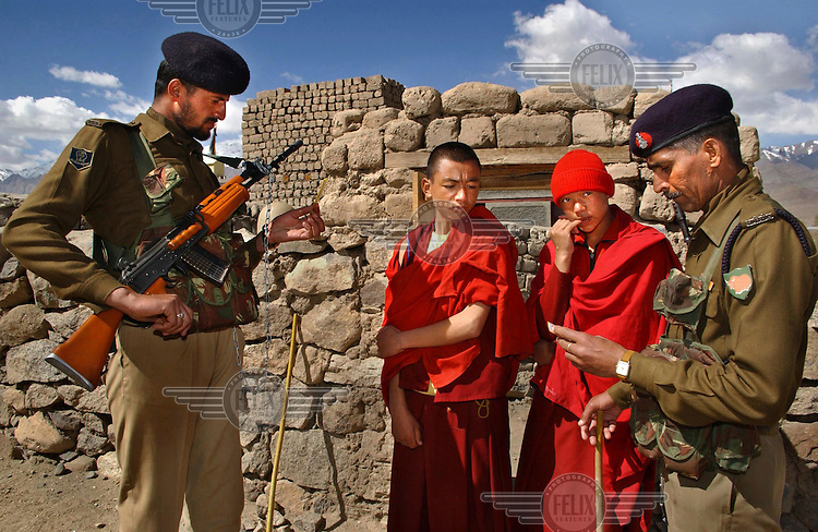 Indian security check the identification of Ladakhi Buddhists from the Thiksey Monastery who wait to cast their votes in the last round of elections in the mountainous region around Leh.