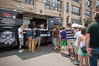 Hipsters line up at the Action Bronson food truck at the annual Bushwick Block Party in the Bushwick neighborhood of Brooklyn on Saturday, July 27, 2013. Young adults came from all over to listen to music and to hang out with their friends and neighbors.  The party took place on Moore Street and was organized by the street's most well know resident, Roberta's Pizza. (©Richard B. Levine)