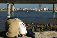 """A young Indian couple. The fort area in Mumbai is very popular with young people, """"lovers Lane or better better called beach"""", every afternoon, getting away from trafic and the city..The view from the fort area towards the other side of Mumbai,India"""
