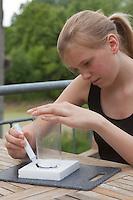 Mädchen, Kind bastelt eine Becherlupe, Beobachtungsgefäß aus 2 durchsichtigen Plastikbecher, einem Stück Styropor und Frischhaltefolie. 1. Schritt: Bechergroßer Kreis wird auf Styroprplatte aufgemalt