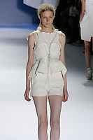 Julia Nobis walks runway in a White super pique peplum tailored vest with oversized hood over white textures silk sleeveless top, and White super pique skirted short, by Vera Wang, for the Vera Wang Spring 2012 collection, during Mercedes-Benz Fashion Week Spring 2012.