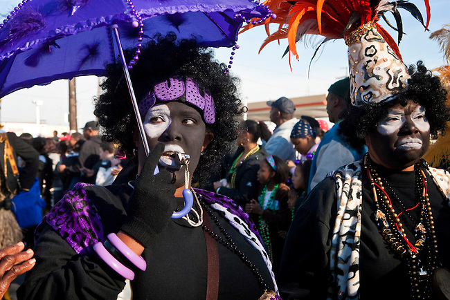 Costumed and painted face members of the Zulu Social Aid and Pleasure Club parade through the streets on Mardi Gras day near Claiborne Avenue in New Orleans, Louisiana, USA.