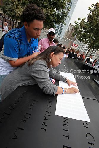 On the 10th anniversary of the September 11th attacks, Milly Checo (right), who lost her husband Pedro Francisco Checo in Tower 2, traces his name as her son, Jasen Checo, looks on at the South Memorial Pool at opening day of the September 11th Memorial at the World Trade Center site in New York, New York on Sunday, September 11, 2011..Credit: Jefferson Siegel / Pool via CNP