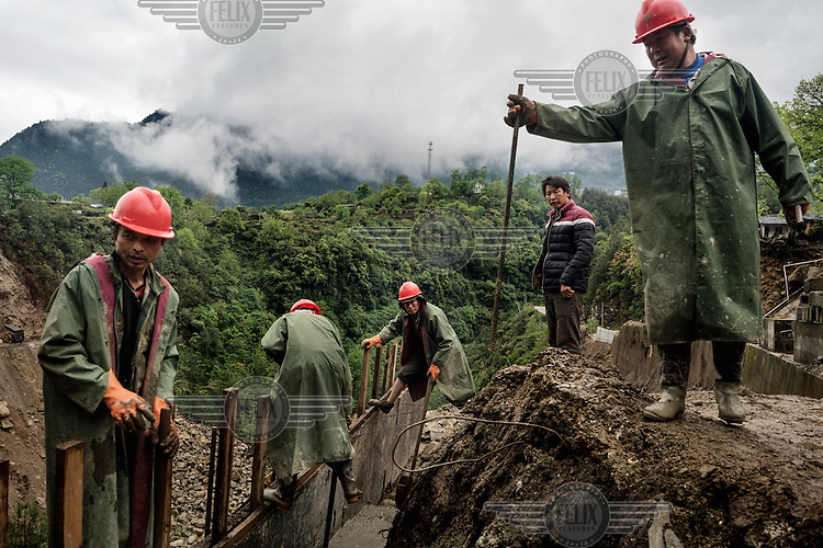 Migrant construction workers from Chu Xiong in central Yunnan building a bridge as part of the extension of the road along the Nujiang River to Tibet, a major government project hoping to bring tourism to the region. They arrived a few months ago and are here for two years to build three bridges. The workers are paid 200 Yuan (22.50 GBP) per day, but if it rains and they can't work, as it often does in the rainy season, they are not paid.