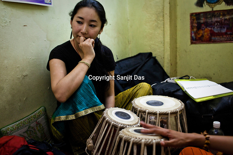 Mina, a japanese tabla student during her tabla lesson in a small shop in the ancient city of Varanasi in Uttar Pradesh, India. Photograph: Sanjit Das/Panos