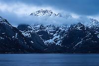 Klokktind mountain peak emerges from clouds over fjord, Toppøya, near Reine, Moskenesøy, Lofoten Islands, Norway