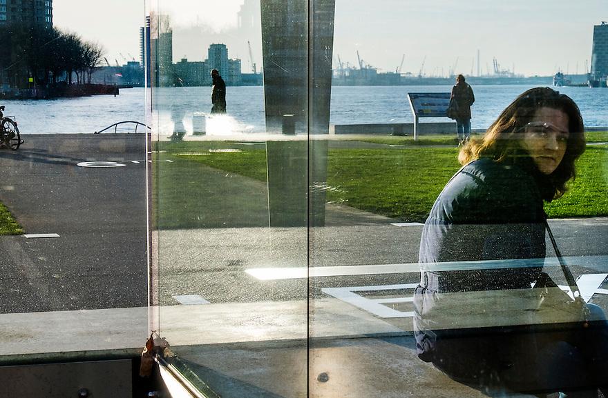 Nederland, Rotterdam, 12 jan 2014<br /> Kop van Zuid. Vrouw achter het glas van een terras. <br /> <br /> Foto: Michiel Wijnbergh