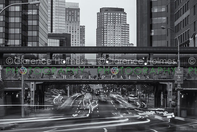 Traffic creates light trails under the welcome sign on the Metro-North overpass entering downtown White Plains, New York