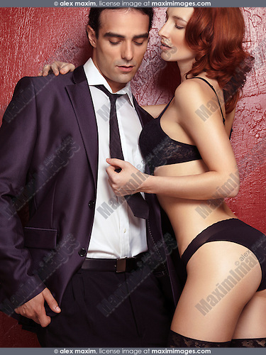 Couple portrait of young man in a suit and sexy red-haired woman in lingerie holding him by the necktie on red background