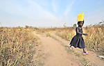 A girl carries water home from a well provided by the United Methodist Committee on Relief, in Yei, Southern Sudan.