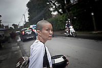 MAE CHEE TIAP goes toward a Public Kindergarden where she teachs after had collected charity in the neighborhood streets. She has been professor during 2 years and ordained as a nun since 2 months, but served as volunteer during several years at the Sathira Dhammasathan centre. Dressed in white-clad, she keeps the eight precepts and has her head and eyebrows shaved when she teachs at the Kindergarden, where children learn to pray and offer salutations to Buddha every morning.