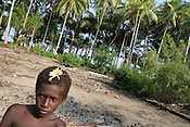 "A child with a flower in his hair, in the ""garden"", an area formerly used for growing crops, but now barren and destroyed by salt sea water waves, on Puil Island, Carteret Atoll, Papua New Guinea, on Sunday, Dec. 10, 2006.  Rising sea levels have eroded much of the coastlines of the low lying Carteret islands (situated 80km from Bougainville island, in the South Pacific), and waves have crashed over the islands flooding and destroying what little crop gardens the islanders have. Food is in short supply, banana and swamp taro crops are failing due to the salt contamination of the land, and the islanders live on a meagre one meal per day diet of fish and coconut. There is talk by the Autonomous Region of Bougainville government to relocate the Carteret Islanders to Bougainville island, but this plan is stalled due to a lack of finances, resources, land and coordination."