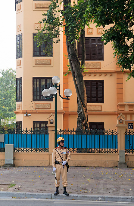 Hanoi Police man on the streets in Hanoi with their lush green trees the capital of Vietnam, is known for its centuries-old architecture and a rich culture with Southeast Asian, Chinese and French influences. At its heart is the chaotic Old Quarter, where the narrow streets are roughly arranged by trade. There are many little temples, including Bach Ma, honoring a legendary horse, plus Đồng Xuân Market, selling household goods and street food.