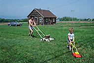 Ile D'Orleans, Quebec City Area, Canada, June 8, 1984. Father and son cutting the grass around the house.