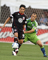 Jaime Moreno #99 of D.C. United shields the ball from Patrick Ianni #4 of Seattle Sounders FC during an MLS match at RFK Stadium on July 15 2010, in Washington DC.Seattle won 1-0.