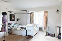 The master bedroom is in the attic and is simply furnished with an unadorned four-poster bed and an uncarpeted wood floor