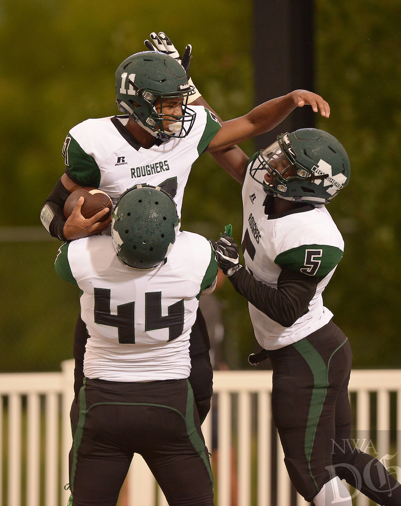 Devin Hillmon (11), Muskogee, Okla. defensive back,  celebrates with teammates Jordan Warren (5) and Philip Duncan (44) after intercepting a Bentonville West pass to score in the first quarter on Friday Sept. 16, 2016 during the game at Tiger Stadium in Bentonville.