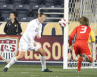 Abby Wambach #20 of the USA WNT heads past Fan Yu #3 of the PRC WNT during an international friendly match at PPL Park, on October 6 2010 in Chester, PA. The game ended in a 1-1 tie.