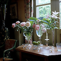 Freshly cut lilies and peony roses from the garden are arranged in a series of glass vases on a console table