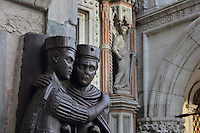 2 Augusti from the statue of the 4 Tetrarchs, sculptural group in porphyry, c. 300 AD, originally in the Philadelphion in Constantinople and moved to Venice in the 13th century, on the corner of the facade of St Mark's Basilica or the Basilica San Marco, Venice, Italy. The Roman Emperor Diocletian set up the Tetrarchy in 293 AD. Behind is the statue of the Allegory of Fortitude, one of the 4 Virtues, on the Porta della Carta, built 1438-42 by Bartolomeo and Giovanni Bon, the entrance to the courtyard of the Doge's Palace or Palazzo Ducale. The city of Venice is an archipelago of 117 small islands separated by canals and linked by bridges, in the Venetian Lagoon. The historical centre of Venice is listed as a UNESCO World Heritage Site. Picture by Manuel Cohen