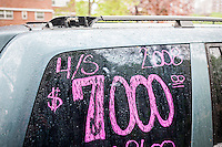 An owner writes the pertinent information on the window of his 8-year old vehicle for sale in the Chelsea neighborhood of New York, seen on Friday, May 6, 2016. (© Richard B. Levine)