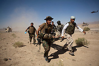 Afghan National Army (ANA) soldiers and a US Army medic from Charlie Company, Sixth Battalion, 101st Aviation Regiment carry a wounded soldier on to a waiting medevac helicopter after his vehicle hit an IED (improvised explosive device) near Kandahar.