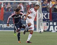 New England Revolution midfielder Lee Nguyen (24) and D.C. United midfielder Perry Kitchen (23) battle for the ball. In a Major League Soccer (MLS) match, the New England Revolution (blue) tied D.C. United (white), 0-0, at Gillette Stadium on June 8, 2013.
