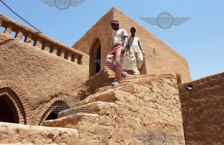 Construction workers descend a set of mud brick stairs at a house in the old quarter of Agadez.