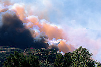 870000355 a los angeles county fire fighting helicopter performs an aerial retardant drop on homes directly in the burn path of the topanga fire in the hills above the san fernando valley in southern california