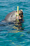 Grand Bahama Island, The Bahamas; a woman hugging a Common Bottlenose Dolphin (Tursiops truncatus) at the water's surface
