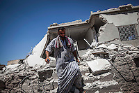 A Syrian civilian walks from a demolished house that has been bombed by daily shelling during night at Anadan village in north of Aleppo.