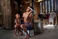 Pedro (Quemon) Tare throws a paper aeroplane as he plays with his son Nampa in the Waorani community of Noneno located beside the Shiripuno River.