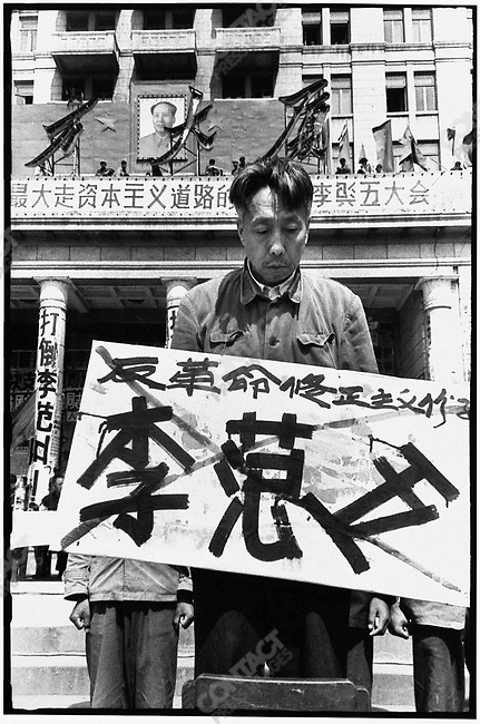 "Forced to stand on chairs in front of the North Plaza Hotel, the seven secretaries of the Heilongjiang Party committee are denounced for ""carrying out Liu Shaoqi's revisionist line."" Each wears a placard with his name crossed out and a description of his alleged crime. Here, Li Fanwu. Harbin, 27 April 1967"