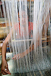 A girl weaving traditional silk cloth under her home in Phonsavan, Xieng Khuang,Laos.