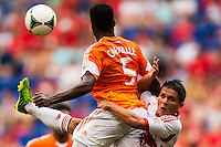 Warren Creavalle (5) of the Houston Dynamo collides with Connor Lade (16) of the New York Red Bulls while going for a header during a Major League Soccer (MLS) match at Red Bull Arena in Harrison, NJ, on June 30, 2013.