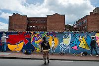 Colombian graffiti artists spray graffiti on the wall in La Candelaria, Bogota, 10 July 2010.