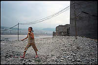 Fengdu, China, August 2003.A little girl playing in the old city of Fengdu, already half-destroyed to allow the Three Gorges Dam project to be completed.