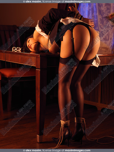 Sexy young asian woman bending over a table tied up with Japanese rope bondage Shibari