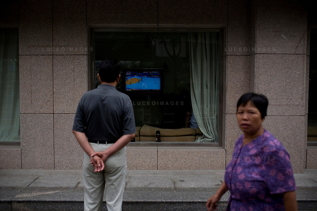 A local resident catches the Olympics while passing by an open window in Beijing, China on Thursday, August 21, 2008.  Kevin German
