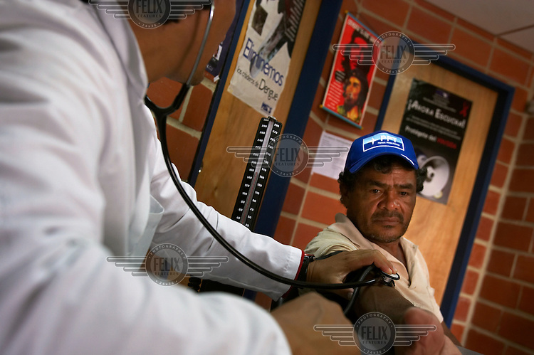 A Venezuelan doctor attends to a patient at a health clinic called Barrio Adentro, which is also staffed by a Cuban doctor. A portrait of Che Guevara hangs on the wall.