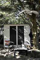 The space under a large pine tree becomes an outdoor living room and the garden shed is transformed into changing rooms for the beach